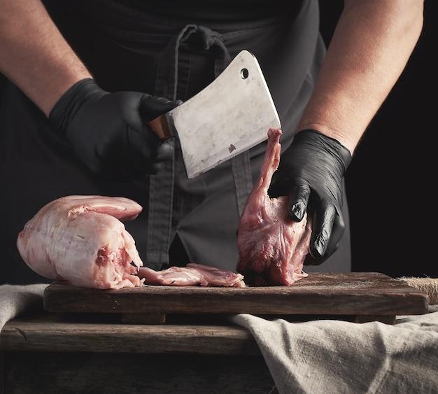 Szef kuchni w czarnych lateksowych rękawiczkach trzyma duży nóż i kroi na kawałki surowe mięso królika