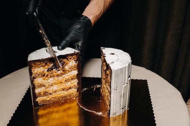 Szef kuchni w czarnych rękawiczkach kroi czekoladowy tort weselny