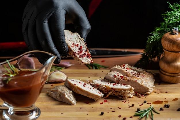 Szef kuchni w czarnych rękawiczkach kroi nożem filet z kurczaka