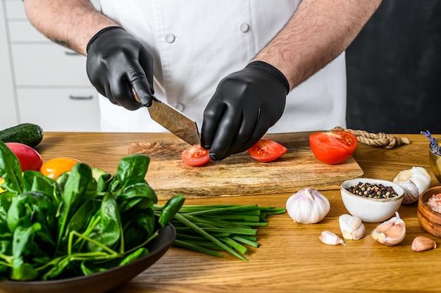 Szef kuchni w czarnych rękawiczkach kroi pomidory na drewnianej desce do krojenia