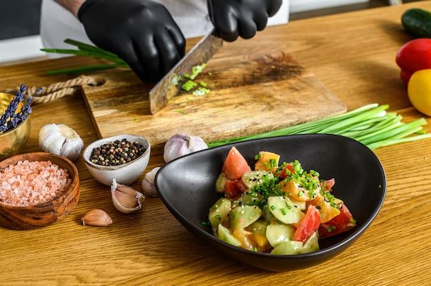 Szef kuchni w czarnych rękawiczkach kroi świeżą zieloną cebulę na drewnianej desce do krojenia.