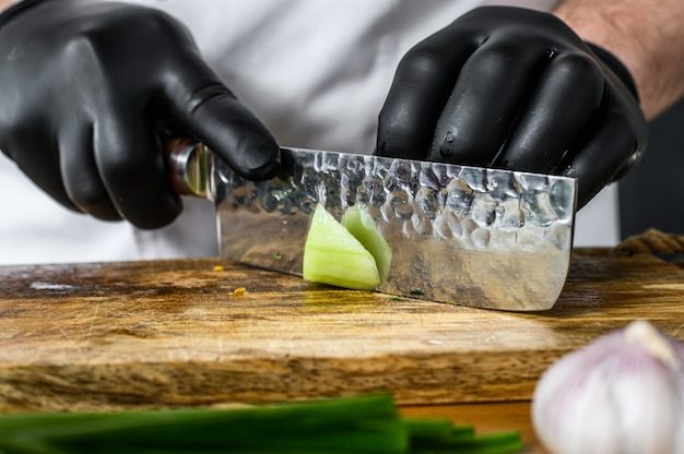 Szef kuchni w czarnych rękawiczkach kroi świeżego zielonego ogórka na drewnianej desce do krojenia. koncepcja gotowania zdrowej żywności ekologicznej