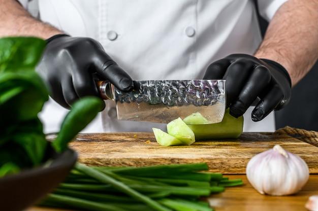 Szef kuchni w czarnych rękawiczkach kroi świeżego zielonego ogórka na drewnianej desce do krojenia.