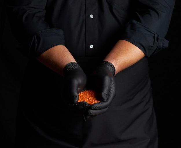 Szef kuchni w czarnych rękawiczkach lateksowych trzyma w dłoniach surową soczewicę, z bliska
