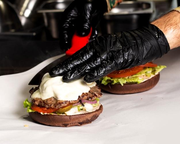 Szef kuchni w czarnych rękawiczkach przygotowuje burgera wołowego