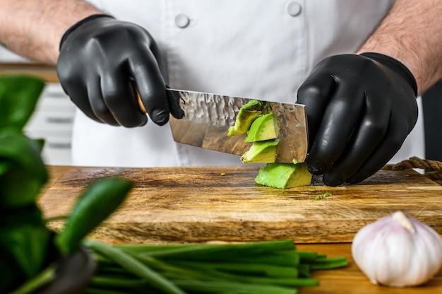 Szef kuchni w czarnych rękawiczkach przygotowuje guacamole ze świeżego awakado.