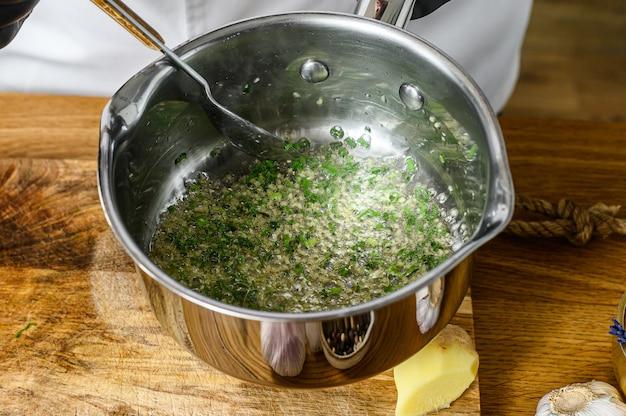 Szef kuchni w czarnych rękawiczkach przygotowuje smażone warzywa. koncepcja gotowania zdrowej żywności ekologicznej