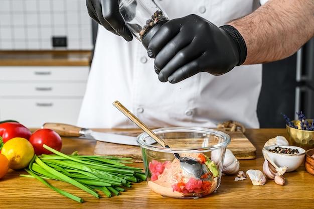 Szef kuchni w czarnych rękawiczkach przygotowuje tatar ze świeżego tuńczyka.