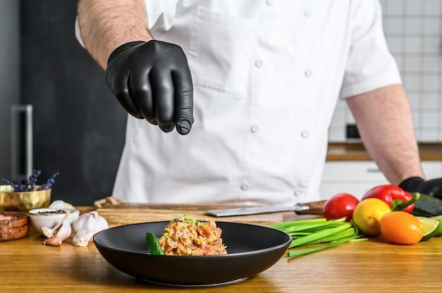 Szef kuchni w czarnych rękawiczkach przygotowuje tatar ze świeżego tuńczyka