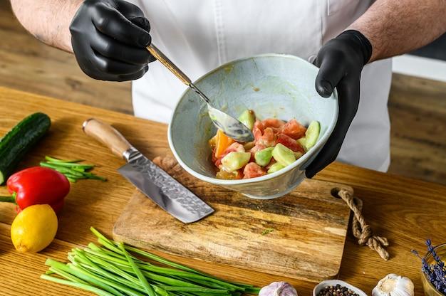 Szef kuchni w czarnych rękawiczkach przygotowuje wegetariańską sałatkę warzywną.