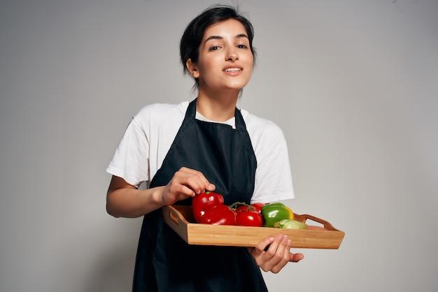 Szef kuchni w czarnym fartuchu warzywa świeże jedzenie na białym tle