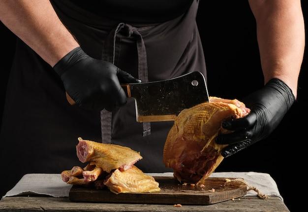 Szef kuchni w czarnym mundurze i lateksowych rękawiczkach sieka surowego kurczaka na kawałki