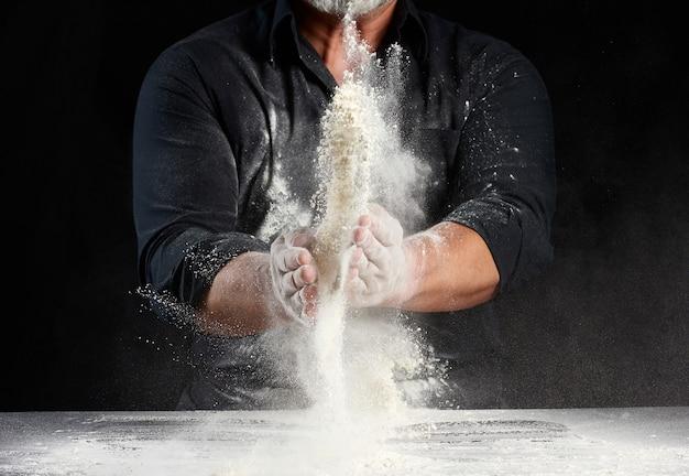 Szef kuchni w czarnym mundurze posypuje białą mąkę pszenną w różnych kierunkach, produkt rozprasza kurz, czarna przestrzeń, mężczyzna siedzący przy stole