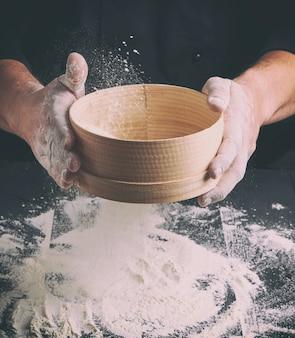 Szef kuchni w czarnym mundurze trzyma w ręku okrągłe drewniane sito