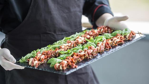 Szef kuchni w hotelu lub restauracji, trzymając w dłoniach łupkową deskę z sałatką caprese.