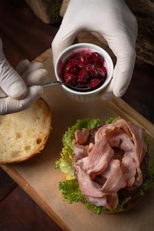 Szef kuchni w jednorazowych rękawiczkach dodaje sos wiśniowy do świeżego rzemieślniczego burgera wołowego ze smażonymi plastrami boczku i świeżą sałatą przed podaniem go klientowi