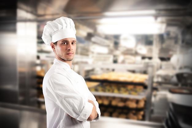 Szef kuchni w kapeluszu i fartuchu w kuchni restauracji