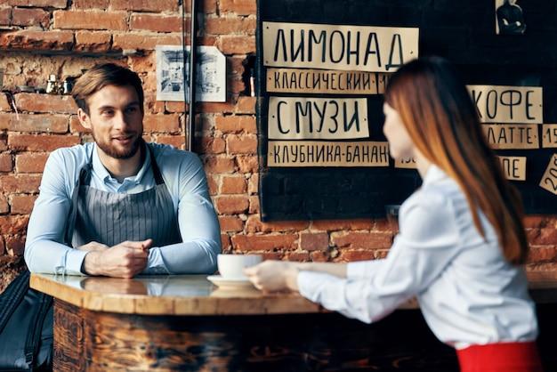 Szef kuchni w kawiarni bar ceglana ściana klienci menu wnętrze pokoju kubek do picia