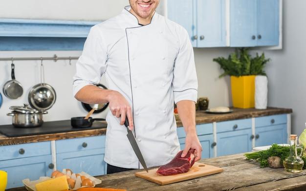 Szef kuchni w kuchni cięcia mięsa