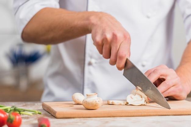 Szef kuchni w kuchni gotowanie z warzywami