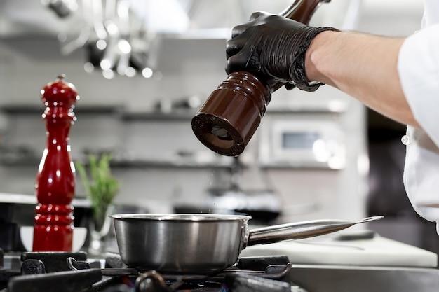 Szef kuchni w kuchni hotelowej lub restauracyjnej, przyprawia potrawy