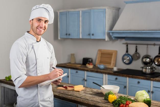 Szef kuchni w kuchni robienia notatek
