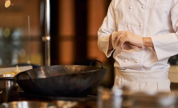 Szef kuchni w mundurze pozuje przy kuchence z wokiem