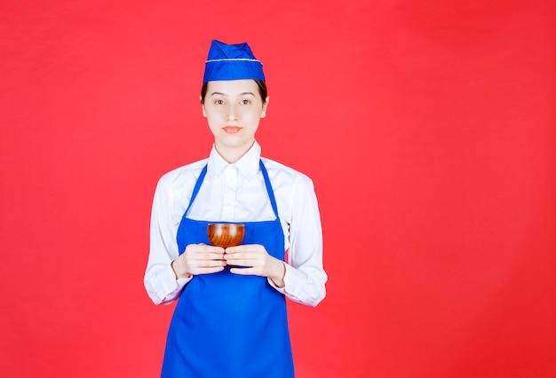 Szef kuchni w niebieskim fartuchu trzyma ceramiczną filiżankę herbaty chińskiej.