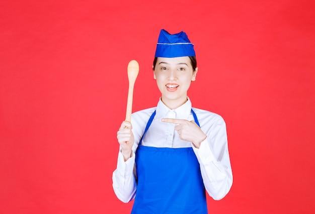 Szef kuchni w niebieskim fartuchu trzyma drewnianą łyżkę.