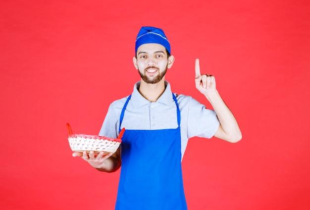 Szef kuchni w niebieskim fartuchu trzyma kosz chleba przykryty czerwonym ręcznikiem i myśli.