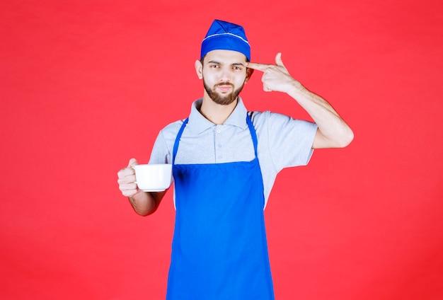 Szef kuchni w niebieskim fartuchu trzymający białą ceramiczną filiżankę i myślący.