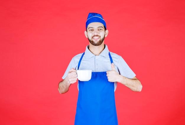 Szef kuchni w niebieskim fartuchu trzymający białą ceramiczną filiżankę i pokazujący znak przyjemności.