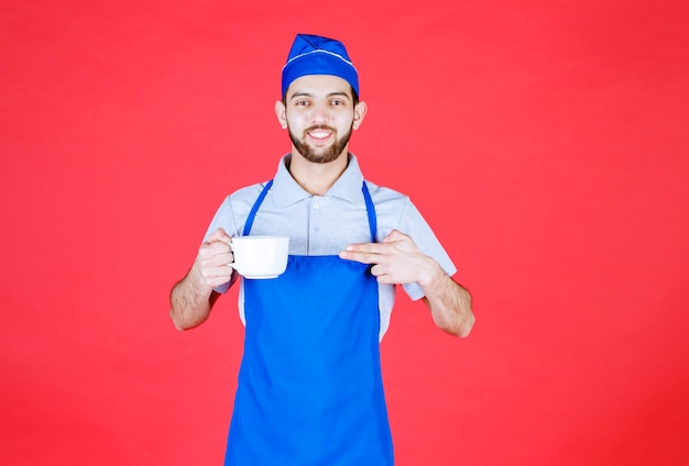 Szef kuchni w niebieskim fartuchu trzymający białą ceramiczną filiżankę.