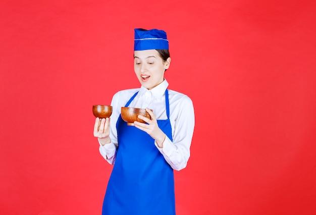 Szef kuchni w niebieskim fartuchu trzymający ceramiczną filiżankę do herbaty, wygląda na przerażonego i zaskoczonego.