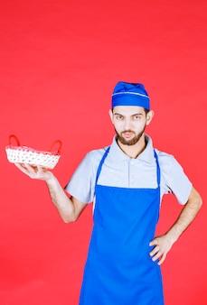 Szef kuchni w niebieskim fartuchu trzymający kosz chleba przykryty czerwonym ręcznikiem.