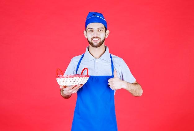 Szef kuchni w niebieskim fartuchu trzymający kosz chlebowy przykryty czerwonym ręcznikiem i pokazujący znak przyjemności.