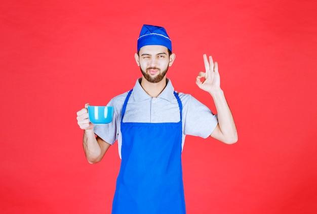 Szef kuchni w niebieskim fartuchu trzymający niebieski ceramiczny kubek i delektujący się smakiem produktu.