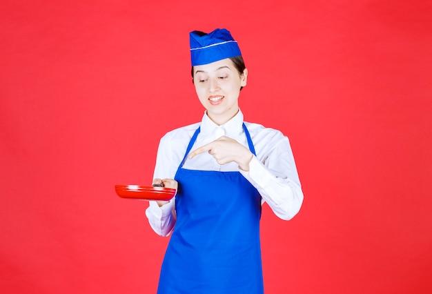 Szef kuchni w niebieskim fartuchu trzymający patelnię tefal.