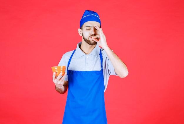 Szef kuchni w niebieskim fartuchu, trzymający żółtą ceramiczną filiżankę i pokazujący znak przyjemności.