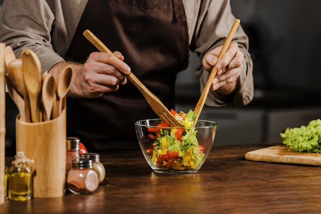 Szef kuchni w połowie strzału mieszający składniki sałatki