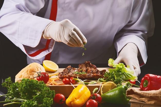 Szef kuchni w rękawiczkach dekoruje stek, posypując natką pietruszki.