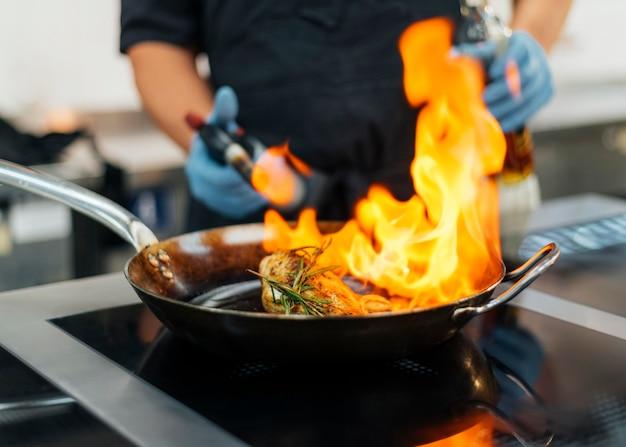Szef kuchni w rękawiczkach płonące naczynie
