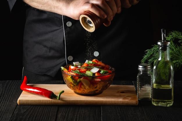 Szef kuchni w restauracyjnej kuchni dodaje papryki do sałatki ze świeżych warzyw