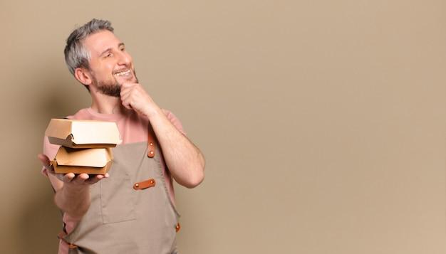 Szef kuchni w średnim wieku mężczyzna z burgerem