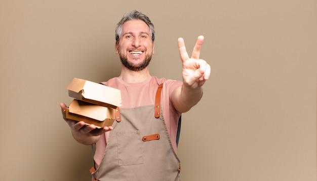 Szef kuchni w średnim wieku z burgerami