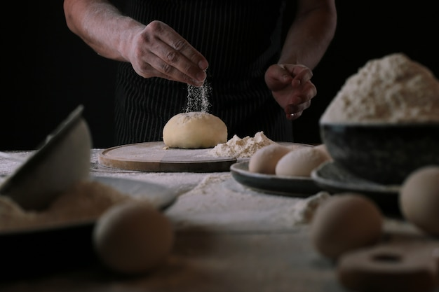 Szef kuchni w trakcie przygotowywania ciasta na pizzę