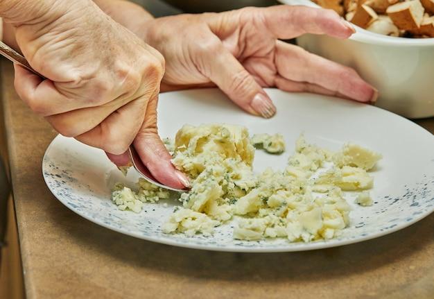 Szef kuchni widelcem ugniata puree ziemniaczane na talerzu.