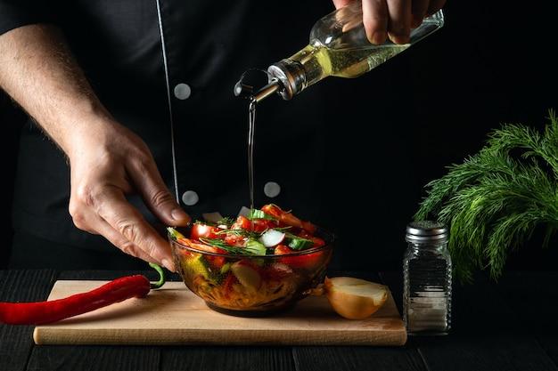 Szef kuchni wlewa oliwę z oliwek do miski sałatki