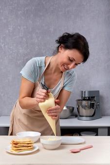 Szef kuchni wlewając śmietanę do miski. proces wytwarzania ciasta.
