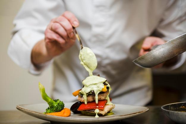 Szef kuchni wlewając sos do posiłku